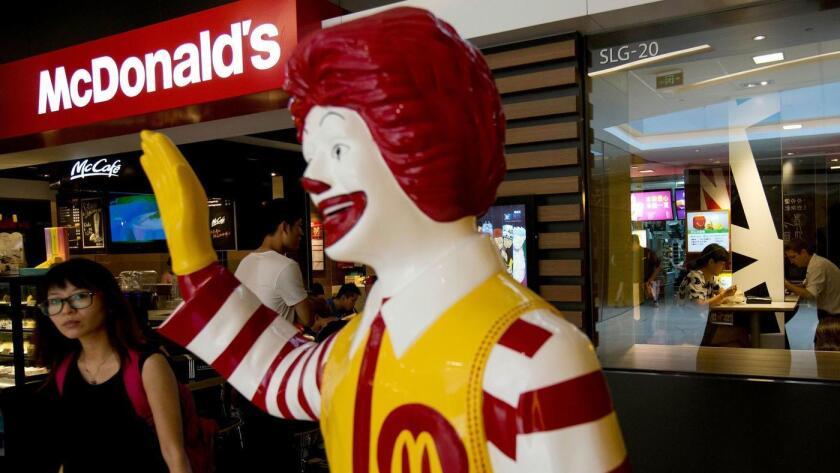 Un cliente junto a la estatua de Ronald McDonald, en el exterior de un restaurante en Beijing, en 2014.