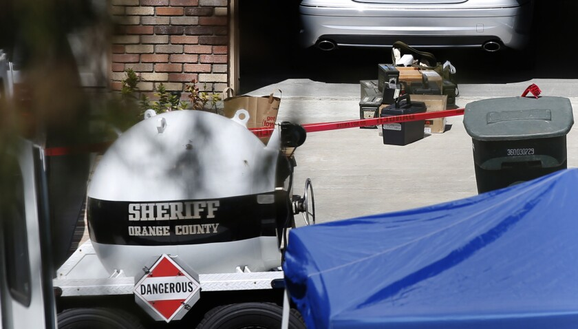 Hazardous explosives sit in the driveway of a home on Fairlane Road in Laguna Niguel, where the Orange County sheriff's bomb squad was sent to evaluate and remove military ordnance found after a domestic disturbance call.