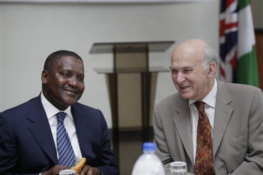 Britain's business secretary, Vince Cable, right, and Nigerian billionaire businessman, Aliko Dangote, left, attend a global business environment meeting in Lagos, Nigeria, Monday, Oct. 8, 2012. The United Kingdom's business secretary said Monday that a bill to overhaul Nigeria's oil industry should be focused on what helps the West African nation, rather than what benefits the foreign oil companies working there. (AP Photo/Sunday Alamba)