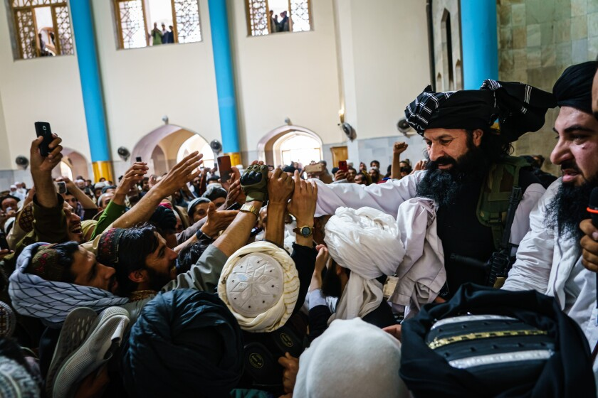 Khalil Rahman Haqqani greets Afghan men
