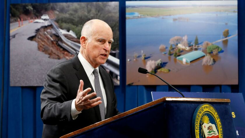 Gov. Jerry Brown discusses his proposal to spend $437 million on flood control and emergency response in the wake of recent storms, during a news conference Friday in Sacramento. In the background are photographs of recent storm damage.