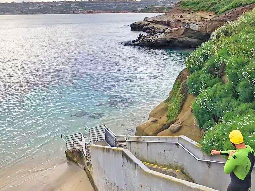 John Shannon is unusally the only swimmer heading toward La Jolla Cove, Friday, March 20, 2020. The state's stay-at-home order allows for going out locally to exercise, if 6-feet social distancing is observed.