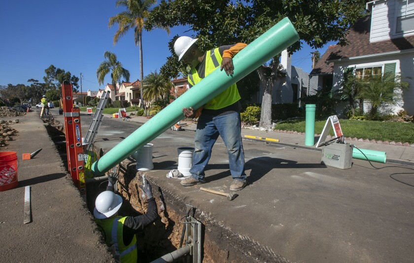 Junior Aguilar lowered pipe into a trench on a sewer replacement project in University Heights in 2020.