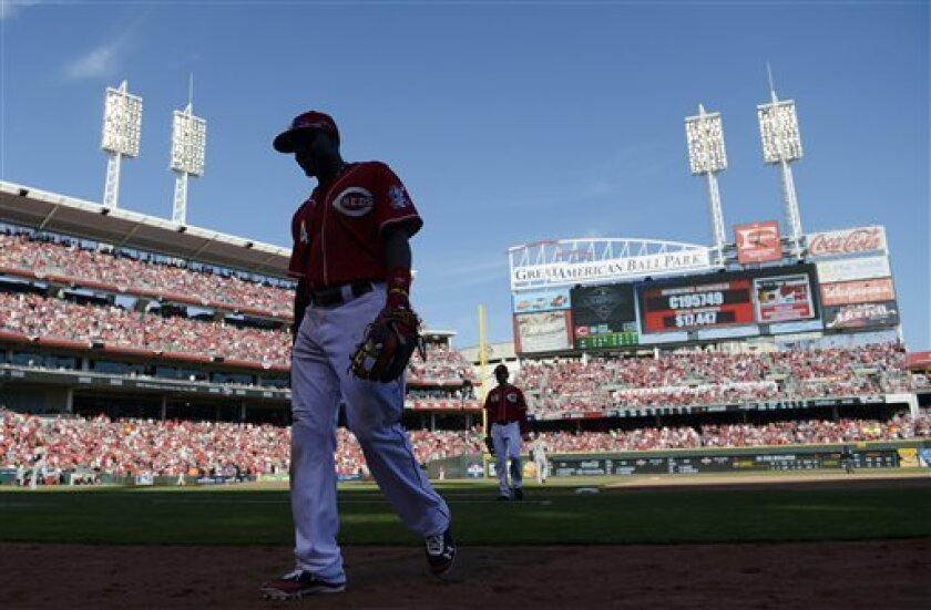 Cincinnati Reds second baseman Brandon Phillips (4) walks off the field for the bottom of the ninth inning of Game 5 of the National League division baseball series against the San Francisco Giants, Thursday, Oct. 11, 2012, in Cincinnati. The Giants won 6-4 and advanced to the NL championship series. (AP Photo/Michael Keating)