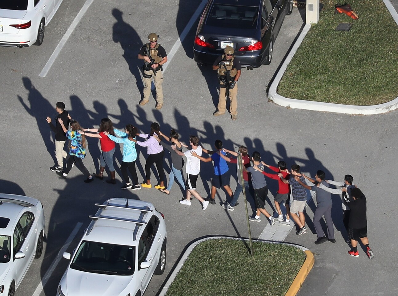 Students are brought out of the Marjory Stoneman Douglas High School after a shooting at the school that killed 17 people on Feb. 14, 2018 in Parkland, Fla.