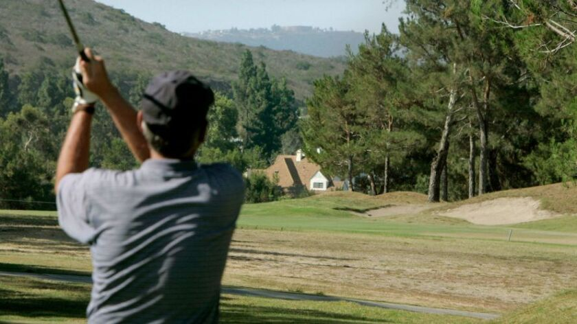 A golfer tees off on a hole at Carmel Mountain Ranch Country Club golf course.