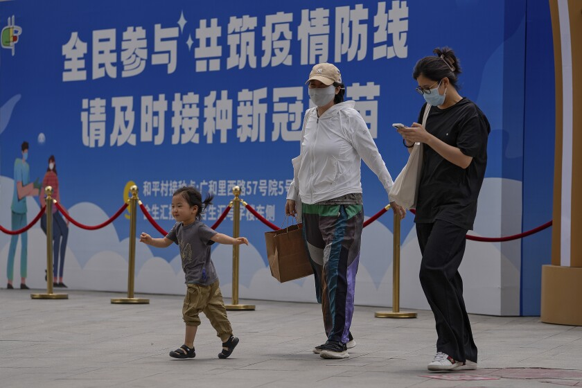 """Women wearing face masks to help curb the spread of the coronavirus and a child walk by a billboard showing the words """"All people participate in building a line of defense against the epidemic, please get the vaccine in time"""" on display outside a shopping mall in Beijing on May 24, 2021. If China is to meet its tentative goal of vaccinating 80% of its population against the coronavirus by the end of the year, tens of millions of children may have to start rolling up their sleeves. (AP Photo/Andy Wong)"""
