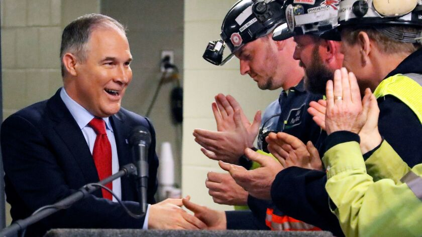 U.S. Environmental Protection Agency Administrator Scott Pruitt, left, shakes hands with coal miners