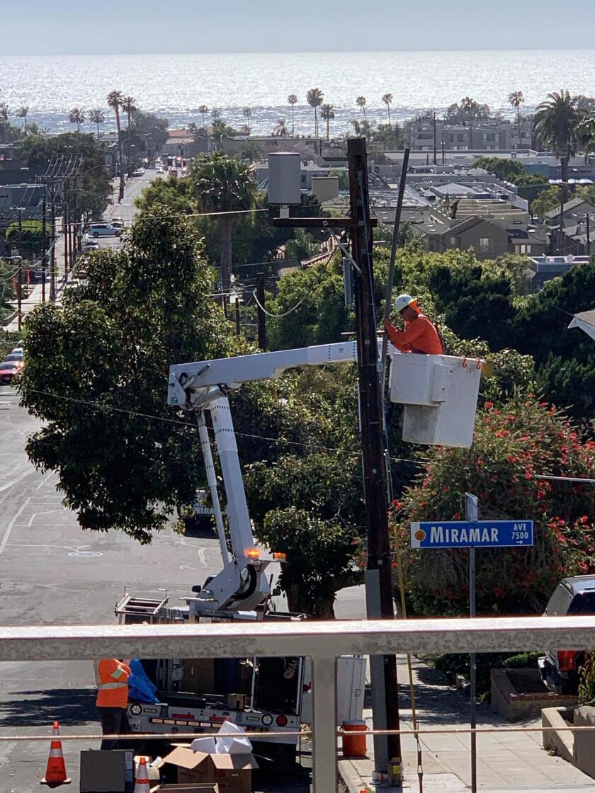 AT&T employees install a 5G miniature, cellular tower on a pole in front of La Jolla resident Harris Cohen's house.