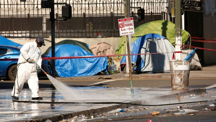 City crews on skid row cleaned East 5th Street Monday near where L.A. Catholic worker Kaleb Havens has been on a hunger strike to demand action by leaders to address the homeless crisis in LA.