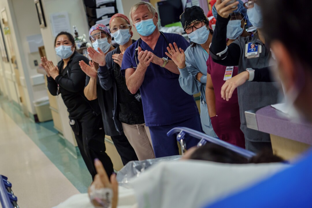 Healthcare workers celebrate as a patient is discharged from the ICU after she was extubated and reocvered from COVID-19 symptoms at Scripps Mercy Hospital in Chula Vista, Calif., on April 23, 2020.