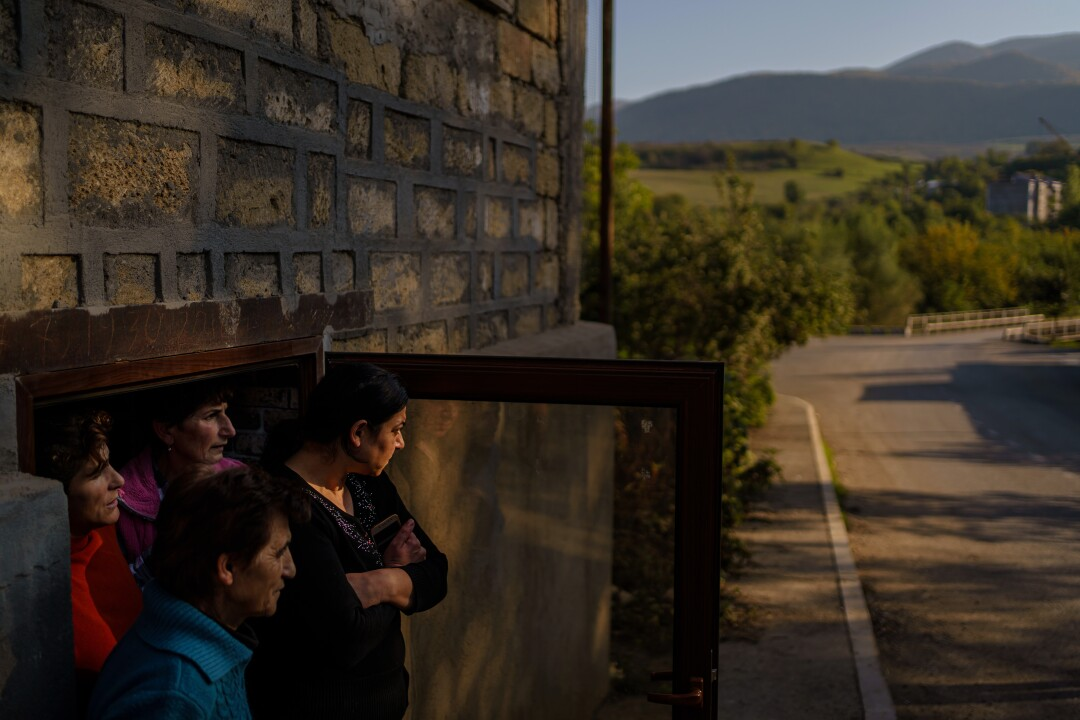 Four resident look out from the doorway of their basement shelter in Karmir Shuka, Nagorno-Karabakh.