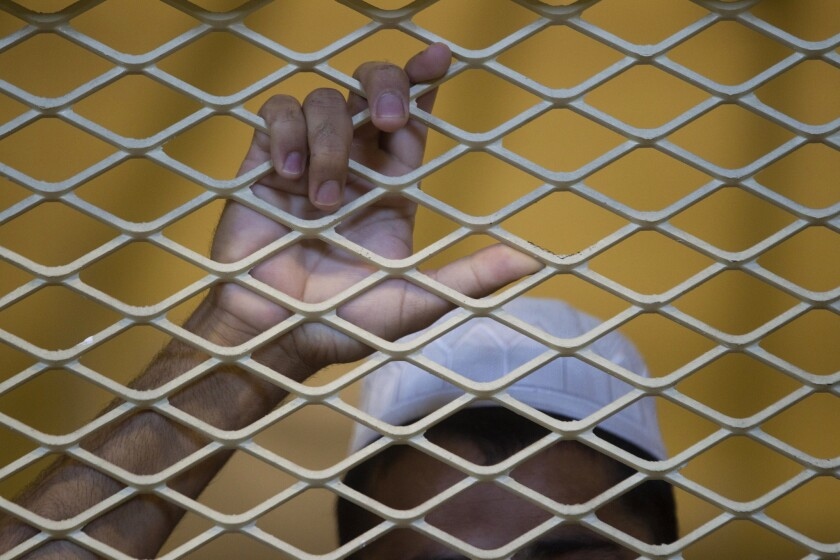 In this file photo reviewed by the U.S. military, a detainee stands in a cell inside the Parwan detention facility near Bagram, north of Kabul, Afghanistan.