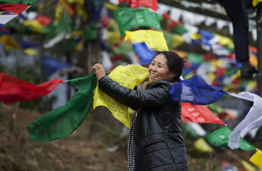 An exile Tibetan holds multi color prayer flags called wind horse or 'lungta' to be tied on tall posts on the third day of the Tibetan New Year, in Dharmsala, India, Thursday, Feb. 11, 2016. Tibetans believe that the Buddhist prayers printed on these flags whose colors represent the five elements,