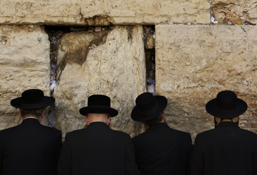 Men face the Western Wall as they pray in Jerusalem.