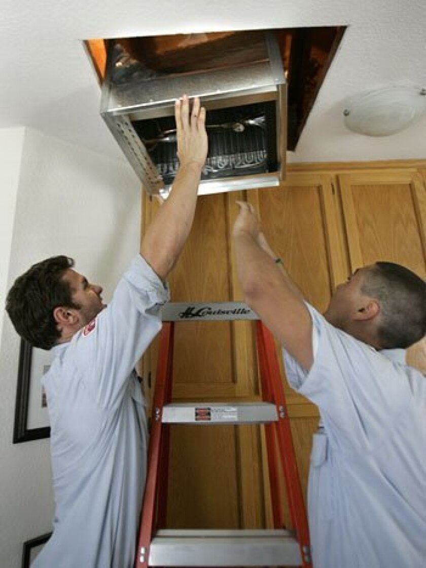 Bill Howe Plumbing technicians Jerrid Alburger (left) and Ryan Cervantes guided a condenser unit into the attic. Workers' comp claims across California have decreased dramatically. (Howard Lipin / Union-Tribune)