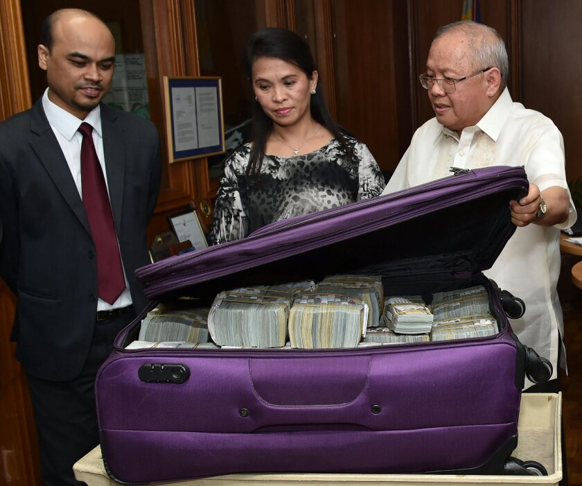 This photo provided by the Bangko Sentral ng Pilipinas, from left, Second Secretary and Head of Chancery of the Bangladesh Embassy in Manila Probash Lamarong, Anti-Money Laundering Council (AMLC) Secretariat Executive Director Julia Bacay-Abad and AMLC Member and Insurance Commissioner Emmanuel Dooc opens a bag containing US dollars that was returned by Chinese casino junket operator Kam Sin Wong to Bangladesh and Philippine AMLC officials in Manila, Philippines on Thursday March 31, 2016. Wong says he has returned $4.63 million of the $81 million that hackers stole from the Bangladesh central bank's account in the U.S. Federal Reserve Bank and laundered in Manila's casinos in one of the world's largest cyberheists. (Jason Arlan Raval/Bangko Sentral ng Pilipinas via AP)