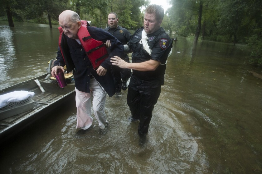 Fred Stewart, left, is helped to high ground by Splendora Police officer Mike Jones after he was rescued from his flooded neighborhood on Thursday in Splendora, Texas.