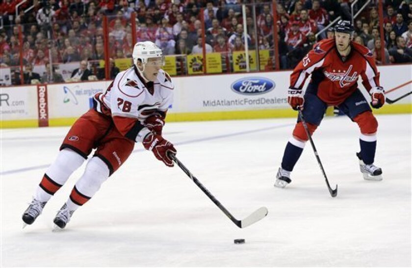 Carolina Hurricanes left wing Alexander Semin (28), from Russia, skates with the puck with Washington Capitals left wing Jason Chimera (25) nearby during the second period of an NHL hockey game Tuesday, Feb. 26, 2013, in Washington. (AP Photo/Alex Brandon)