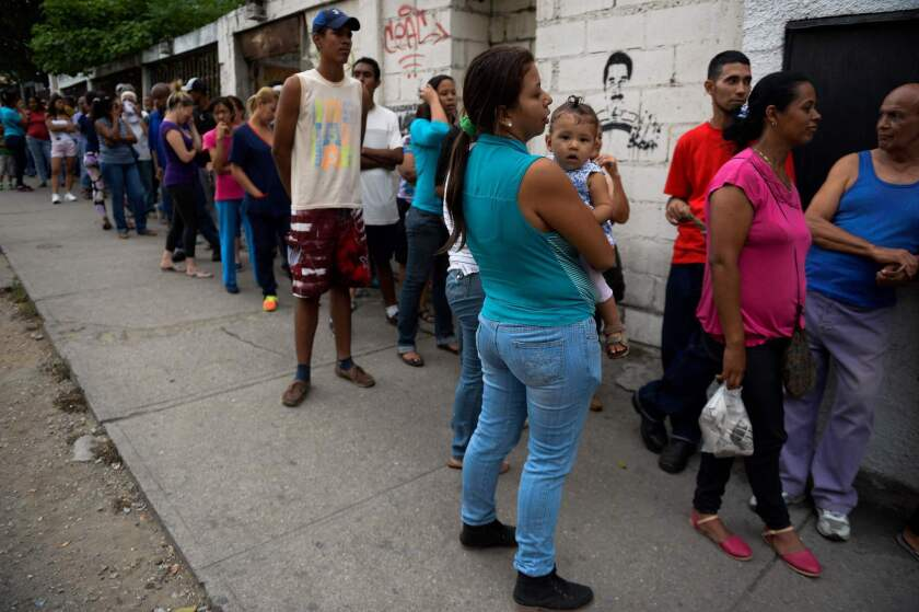 Venezuelans line up to buy bread outside a store in Caracas on May 17, 2016.