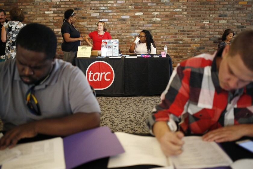 Job seekers fill out employment applications during a Job News USA career fair in Jeffersonville, Ind., on Sept. 20.