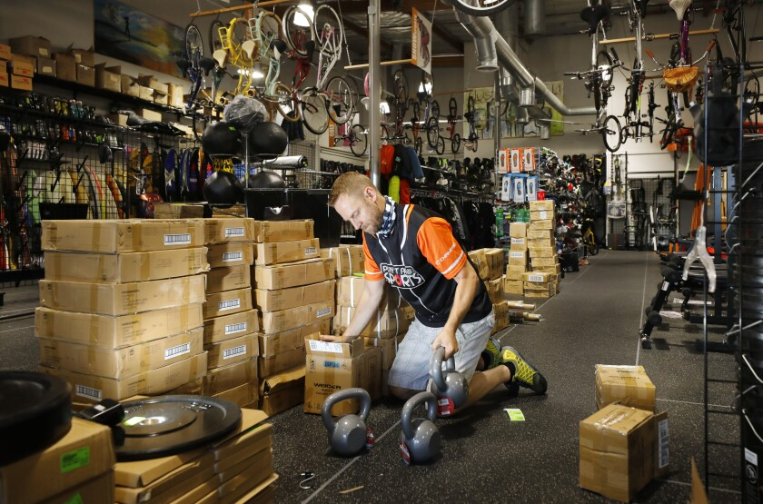 Dan Buxton, owner of Play It Again Sports, stocks weights in the La Mesa sporting goods store.