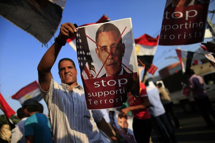 An opponent of ousted Egyptian President Mohamed Morsi burns a poster of President Obama at a rally in Cairo, Egypt.