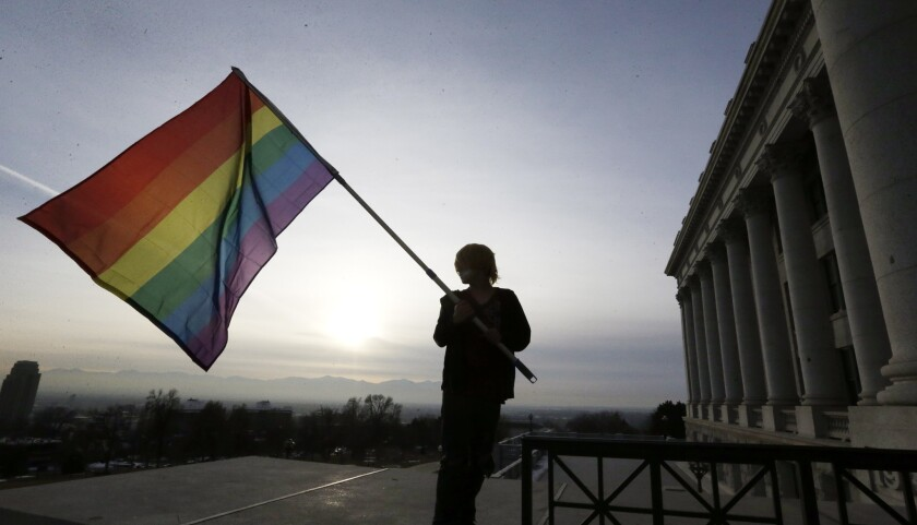 Corbin Aoyagi, a supporter of gay marriage rights, waves a rainbow flag during a rally early this year at the Utah State Capitol in Salt Lake City. The Utah Attorney General's office has petitioned the U.S. Supreme Court to hear its appeal of same-sex marriage.