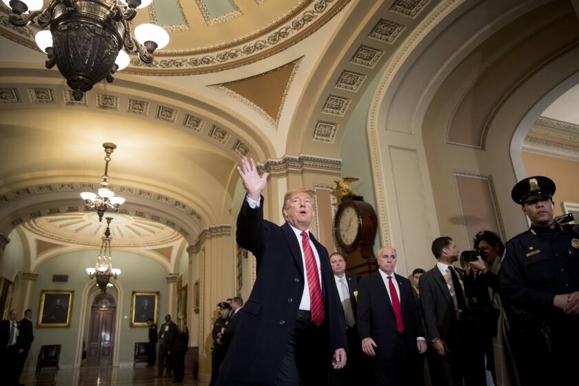 El presidente de Estados Unidos, Donald Trump, acompañado del vicepresidente, Mike Pence, saludan a reporteros a su llegada al Capitolio, en Washington. (AP Foto/Andrew Harnik)