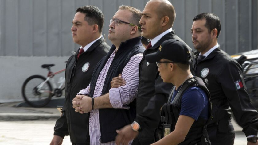 Mexico's former governor of Veracruz state, Javier Duarte, is escorted in handcuffs by police to an aircraft in 2017 as he is extradited to Mexico City