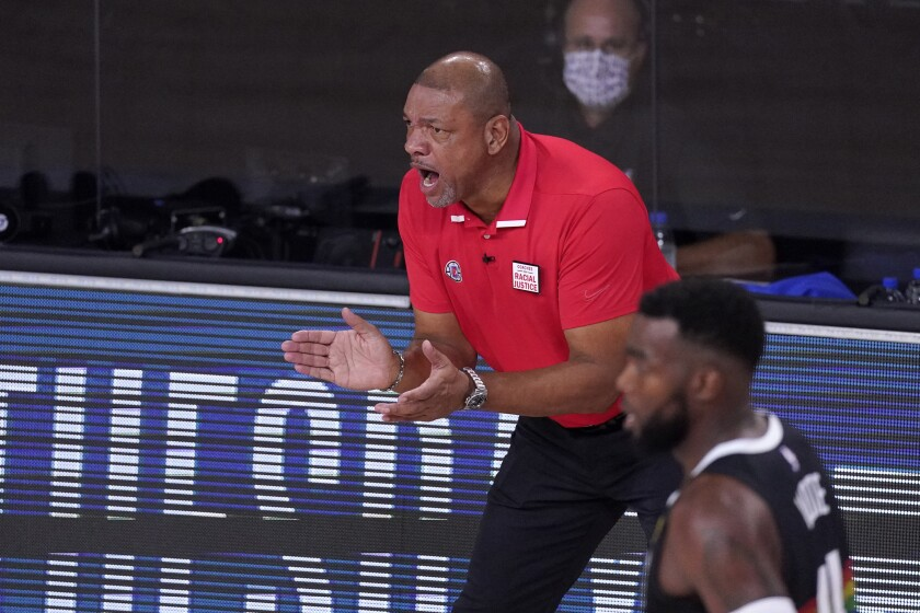 Clippers coach Doc Rivers claps during a game.