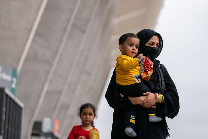 زنی بچه کوچکی را حمل می کند که کیسه ای از تنقلات را در دست دارد