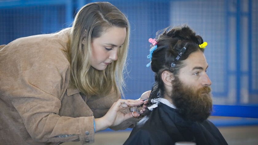 Jenna Freitas, of Escondido, cuts the hair of David Ryan of Fresno during an event held at the Port Pavillion on Broadway Pier in an attempt to break the record for the most hair donated in 24 hours. The hair will be used make wigs for children affected by hair loss.