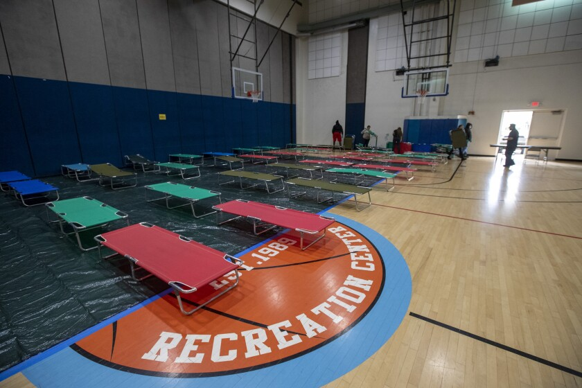 City workers and volunteers from the Salvation Army set up cots at the Westwood Recreation Center in Westwood. It is one of several shelters opening to accommodate homeless people during the coronavirus pandemic.