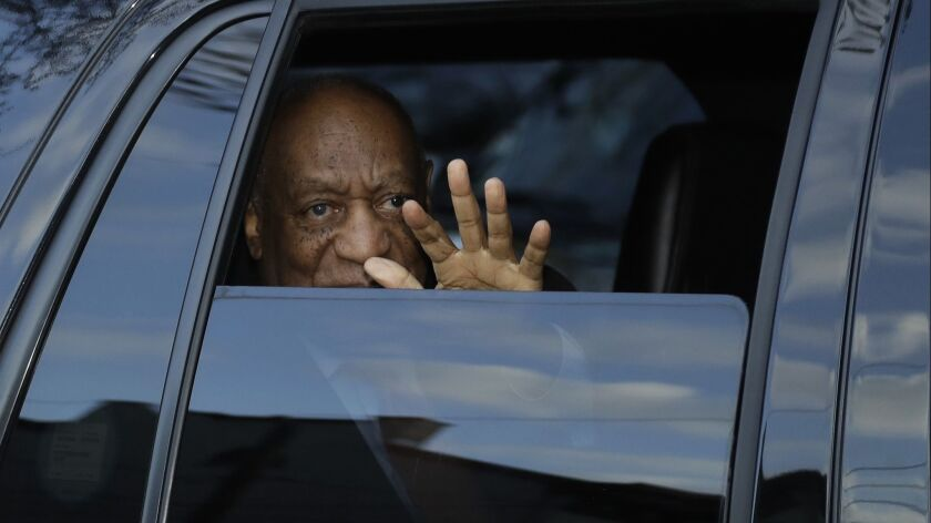 Bill Cosby waves as he leaves the Montgomery County Courthouse in Pennsylvania on Tuesday after proceedings in his sexual assault trial.