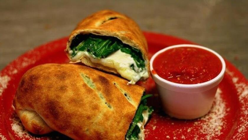 Hot out of the oven spinach roll ($8) at Pizzeria Luigi overflows with mozzarella and ricotta cheese. (Amy T. Granite)