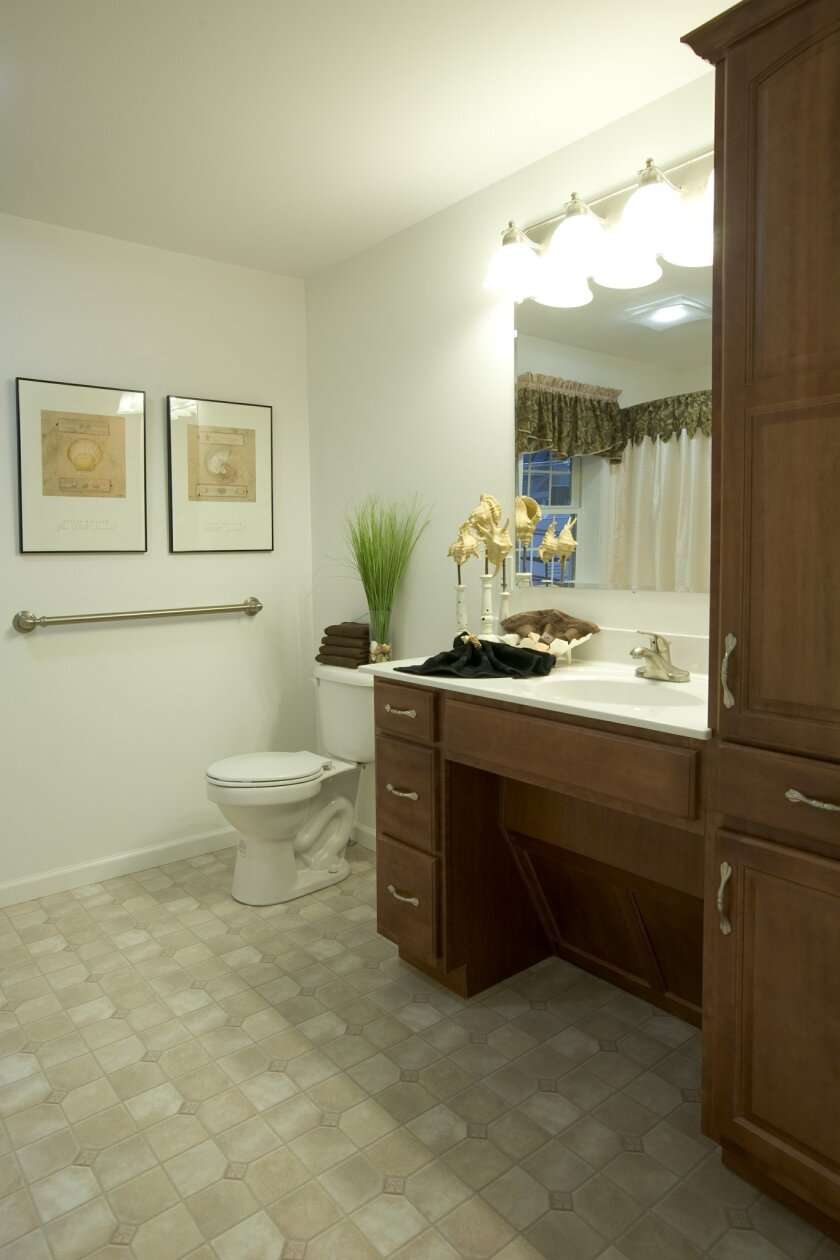 Modifications in the bathroom, including a grab bar near the toilet and an open space under the sink, increase accessibility.