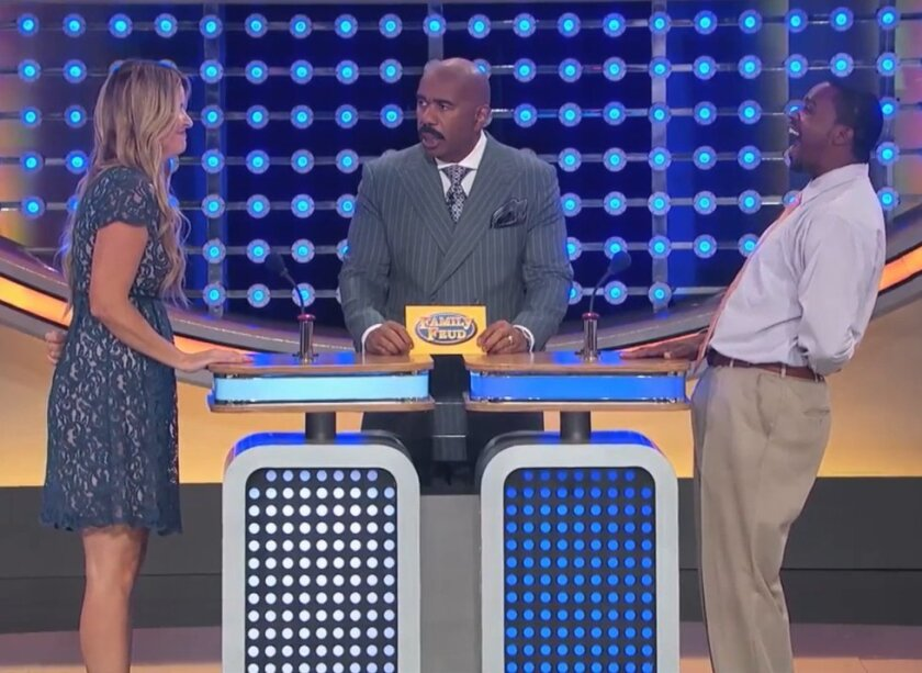 A screenshot of the moment after Darci Circuit (left) gave her surprising answer on 'Family Feud' with stunned host Steve Harvey (center) and the other contestant bursting out in laughter.