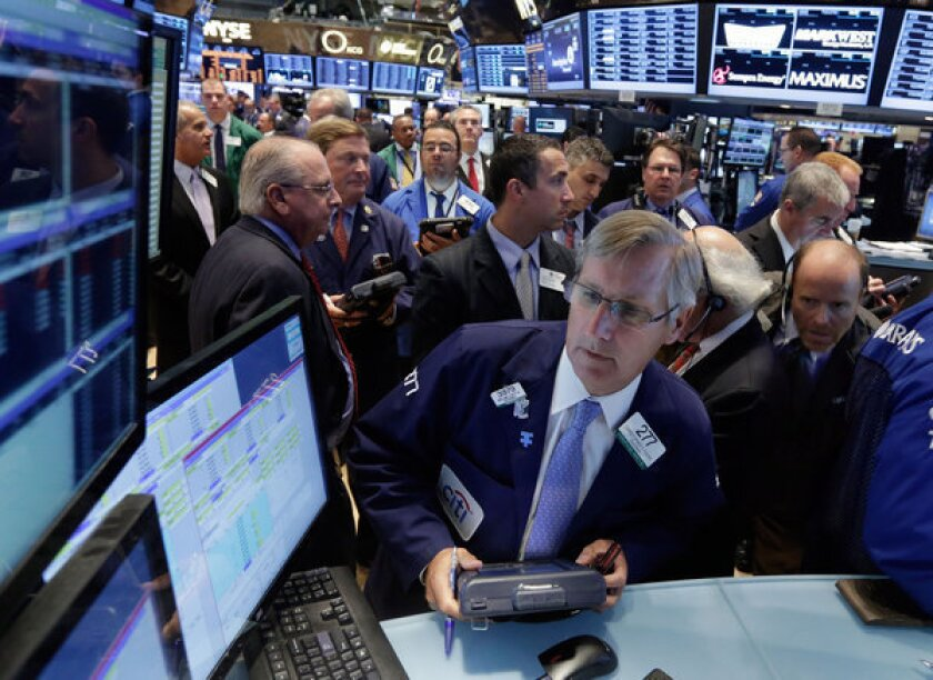 Trader Christopher Fuchs, center, works on the floor of the New York Stock Exchange.