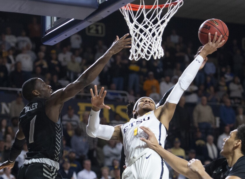 East Tennessee State's Tray Boyd III shoots against UNC Greensboro's Isaiah Miller during a game on Feb. 1.
