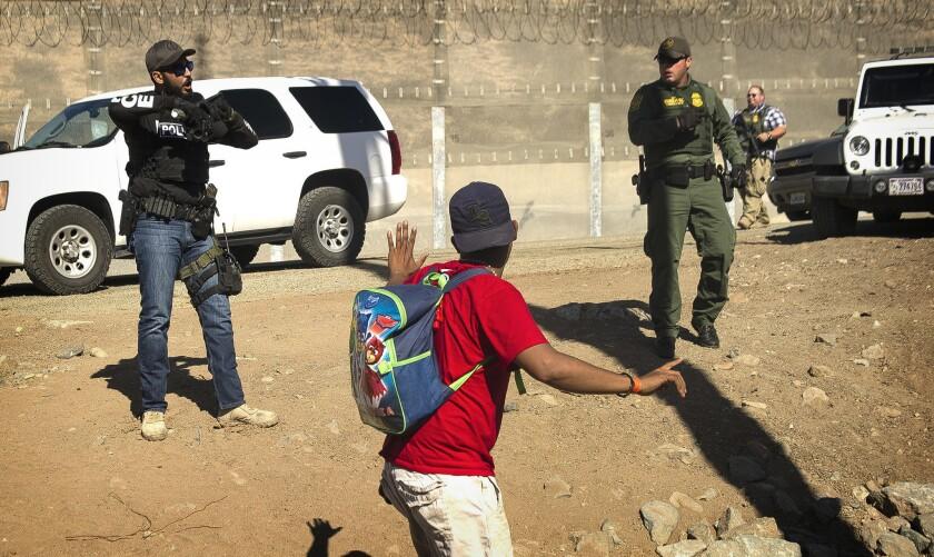 Un migrante centroamericano es detenido por agentes estadounidenses que le ordenaron volver al lado mexicano de la frontera, después de que un grupo de migrantes rebasó a la policía mexicana en el cruce del Chaparral en Tijuana, México, el domingo 25 de noviembre de 2018 en la frontera con San Ysidro, California. (AP Foto/Pedro Acosta)