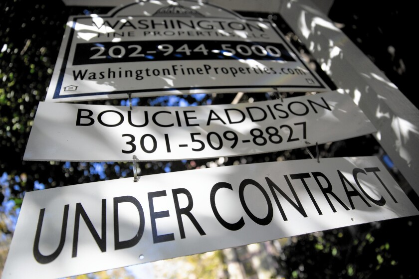 """An """"under contract"""" sign hangs outside a property in Washington, D.C. The """"usual"""" number of people aren't visiting model homes and signing contracts."""