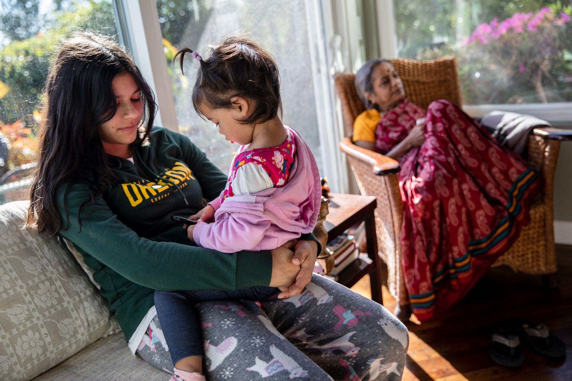 Vishaala Wilkinson holds her 2-year-old sister Lalitha at their home in Del Mar on March 2, 2021.