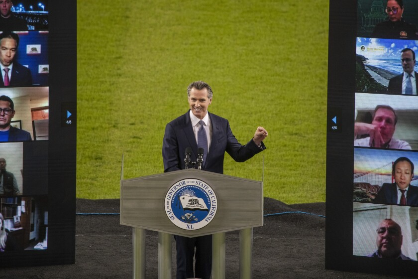 Gavin Newsom gestures from behind a lectern at Dodger Stadium
