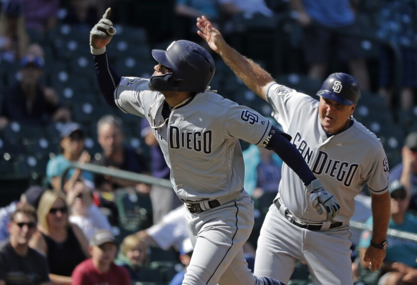 The Padres' Fernando Tatis Jr. runs past third base coach Glenn Hoffman, right, as Tatis Jr. heads for home after hitting a solo home run off Seattle Mariners starting pitcher Yusei Kikuchi during the first inning of a baseball game Wednesday, Aug. 7, 2019, in Seattle.