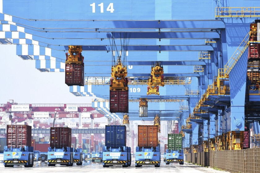 FILE - In this June 4, 2021, file photo, gantry cranes move containers onto transporters at a port in Qingdao in eastern China's Shandong province. China's exports surged in June while import growth slowed to a still-robust level as its economic rebound from the coronavirus leveled off. (Chinatopix via AP, File)