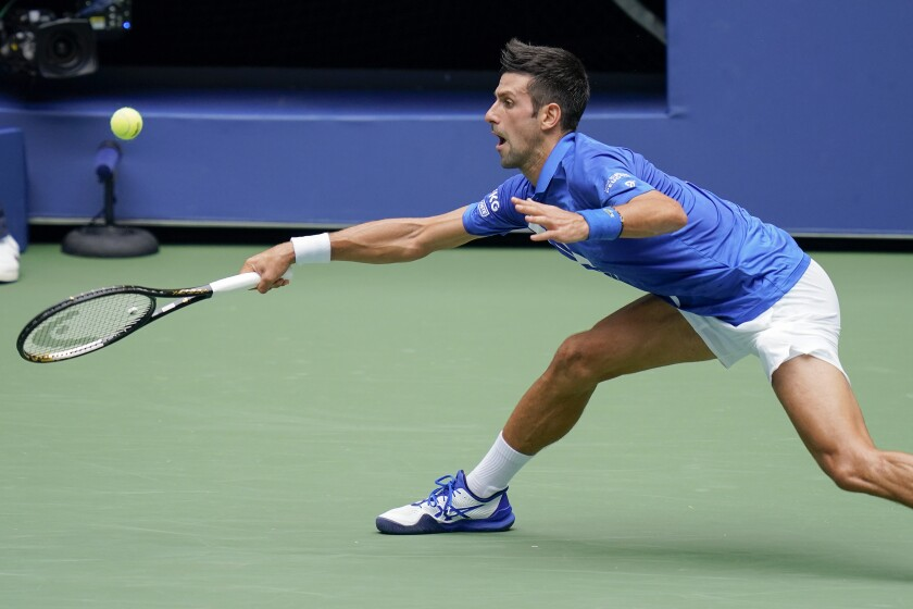 Novak Djokovic, of Serbia, returns a shot to Kyle Edmund, of Great Britain, during the second round of the US Open tennis championships, Wednesday, Sept. 2, 2020, in New York. (AP Photo/Seth Wenig)