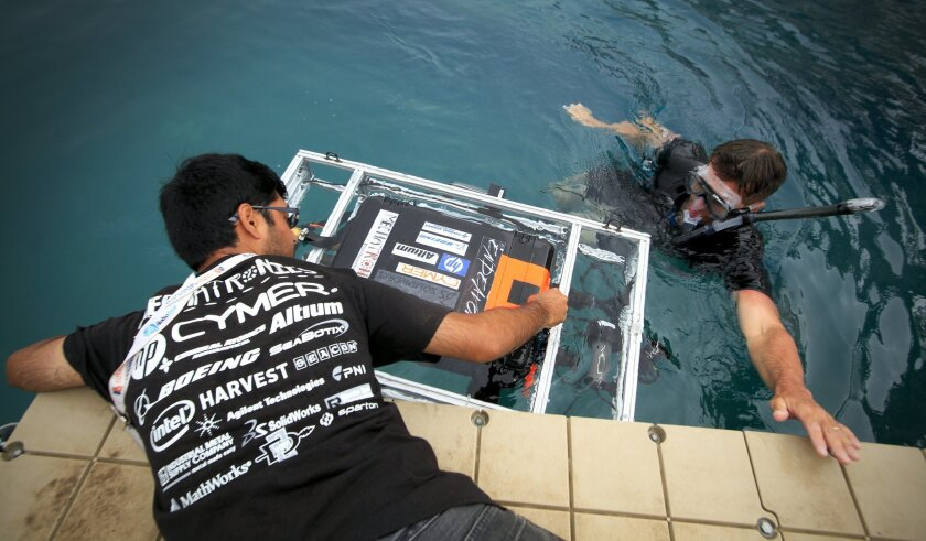 """Akash Khatawate, left, a member of the San Diego State University  Mechatronics Club launches """"Endeavor,"""" as diver, Brian Adams looks on during the 17th annual RoboSub competition for autonomous underwater vehicles held at SPAWAR, Systems Center Pacific Transducer Evaluation Center (TRANSDEC) pool"""