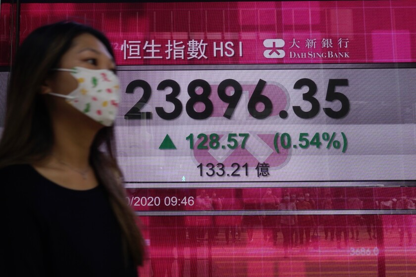 A woman walks past a bank's electronic board showing the Hong Kong share index at Hong Kong Stock Exchange Tuesday, Oct. 6, 2020. Shares advanced in on Tuesday Asia after hopes for economic aid from Washington helped Wall Street recover its losses from the initial shock of learning President Donald Trump had tested positive for the coronavirus. (AP Photo/Vincent Yu)