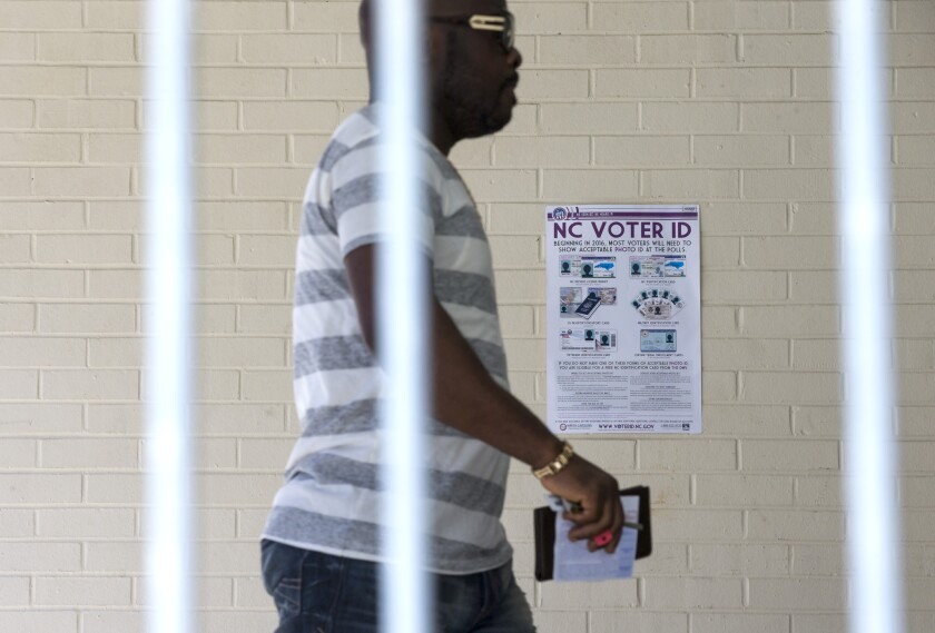 Eric Gandah walks past a voter ID sign as he enters a precinct to cast his ballot in Greensboro, N.C., in March.